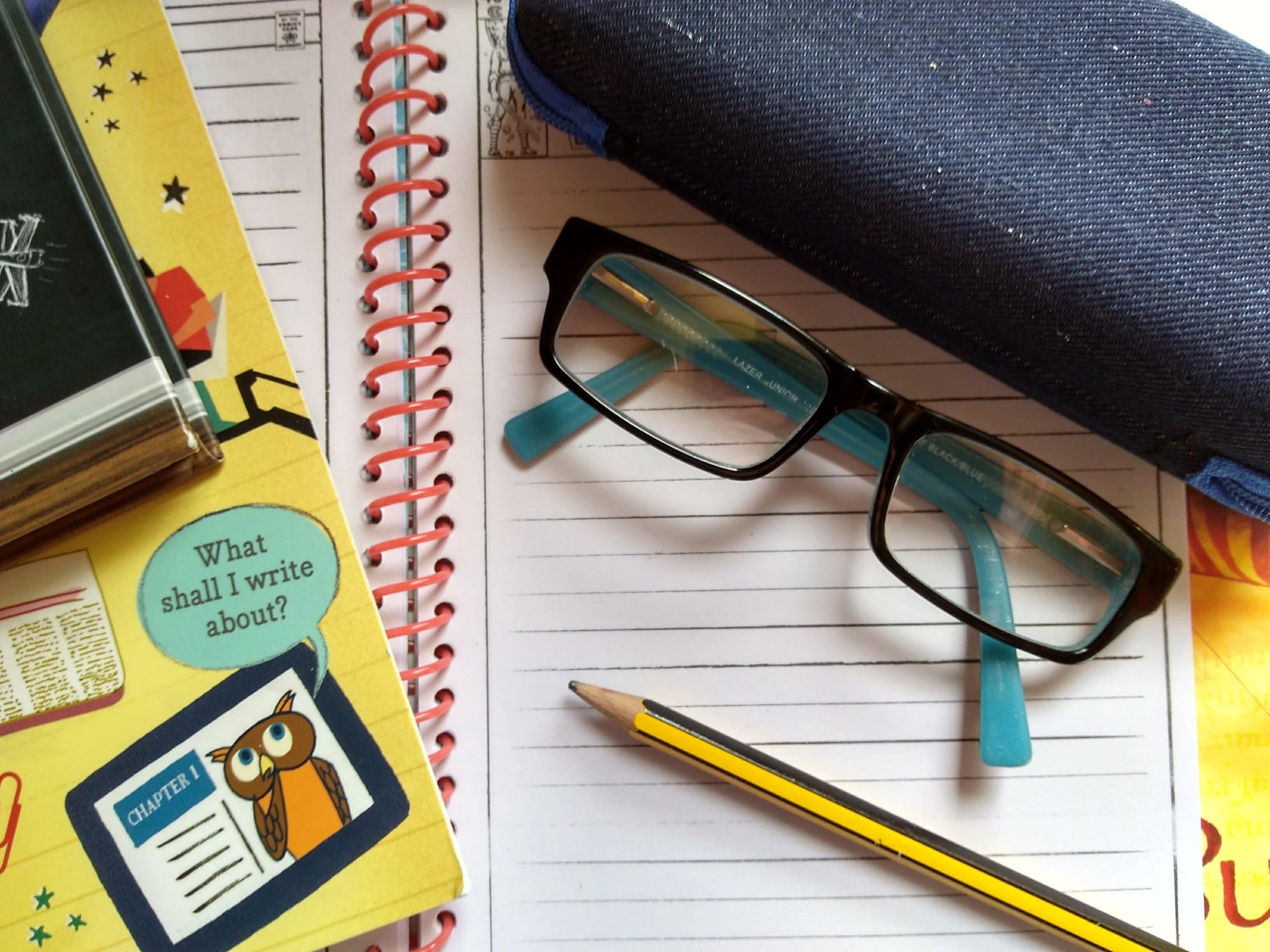 childrens-glasses-for-reading-resting-on-notebook-with-pencil-books-to-side