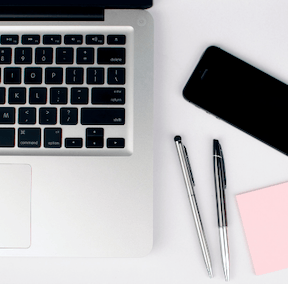 writing tools - laptop, pens and post it notes to help you get to work on your guest post